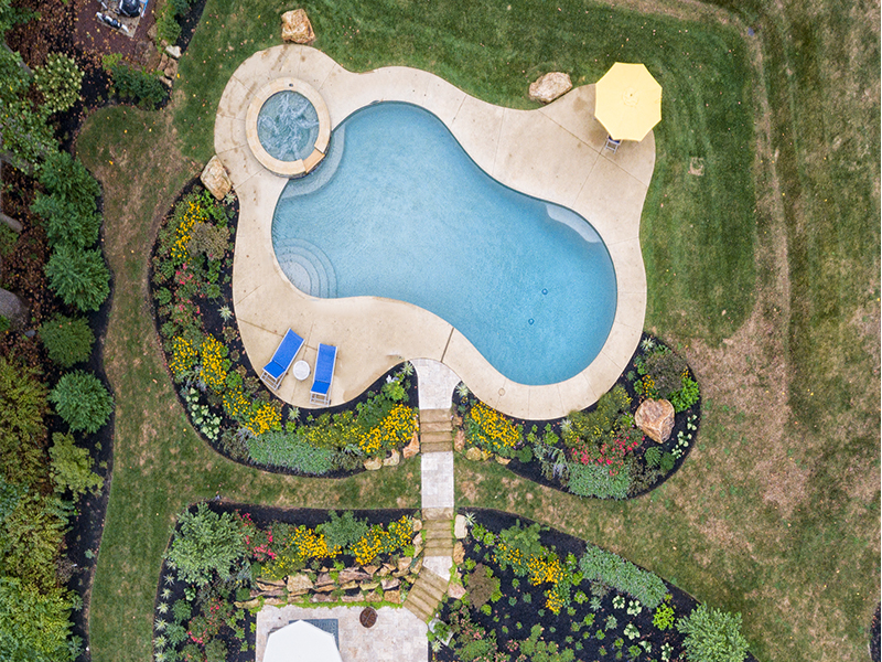 Freeform pool with spa and landscape