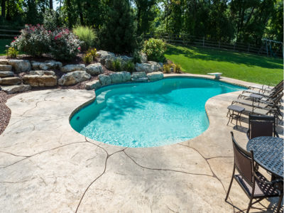 Blue-green pool with stamped concrete deck
